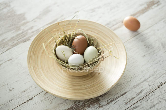 Easter nest with white and brown eggs in bowl on shabby wood — Stock Photo