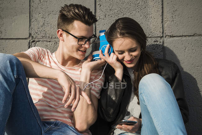 Smiling young couple sharing headphones — Stock Photo