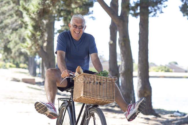 Smiling senior man balancing on bicycle — Stock Photo