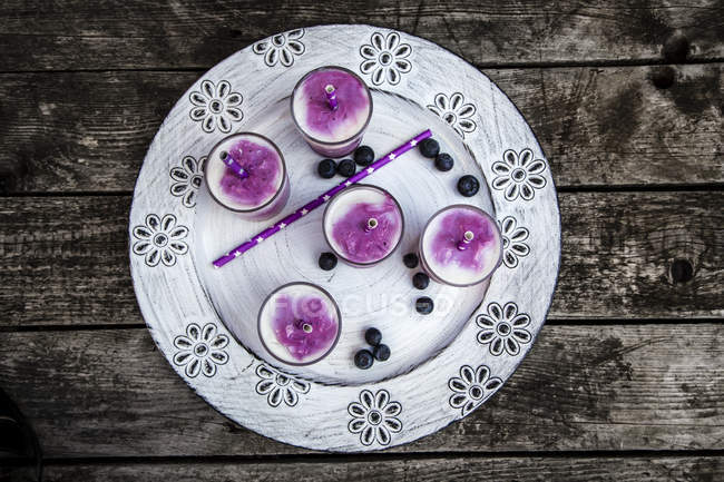 Top view of five glasses of buttermilk blueberry ice cream with drinking straws on tray — Stock Photo