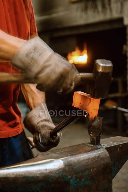 Cropped image of Blacksmith forging hatchet — Stock Photo