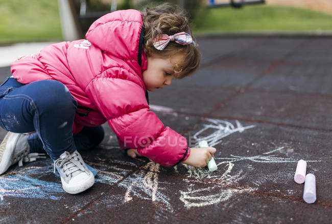 Toddler girl drawing with chalk on ground — Stock Photo