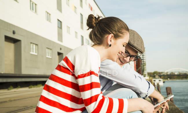 Sorridente giovane uomo e donna all'aperto guardando tavoletta digitale — Foto stock