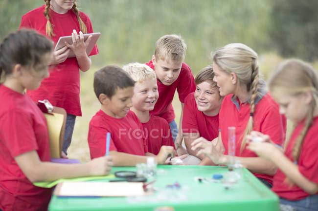 Filhos e mulher de explorar a natureza com equipamento científico — Fotografia de Stock