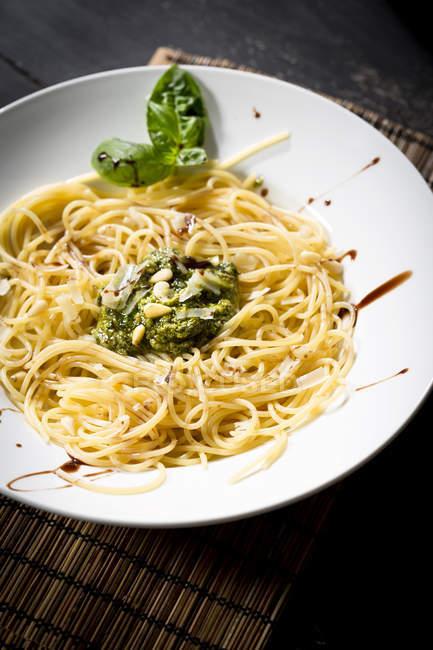 Тарелка спагетти с соусом песто Дженовезе и свежих листьев базилика, вид сверху — стоковое фото