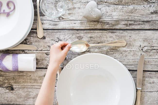 L'impostazione di una tabella, mano con cucchiaio — Foto stock