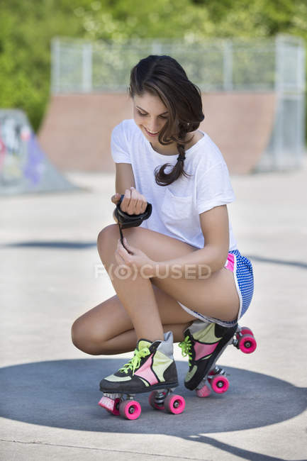 Smiling female inline-skater checking hand protection — Stock Photo