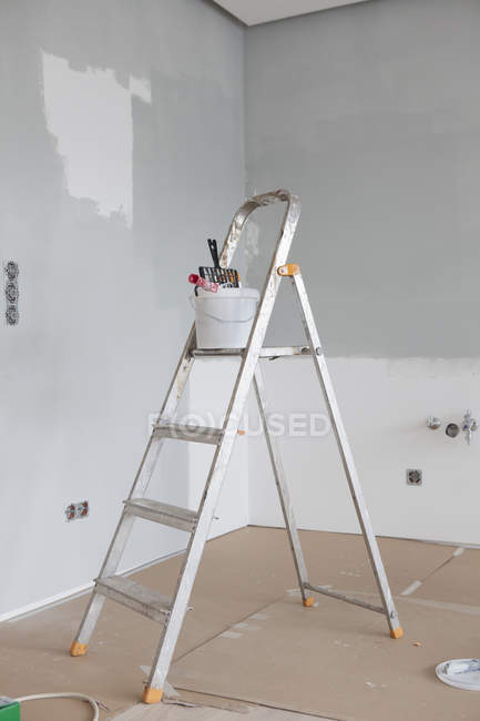 Paint bucket and roll on ladder indoors — Stock Photo