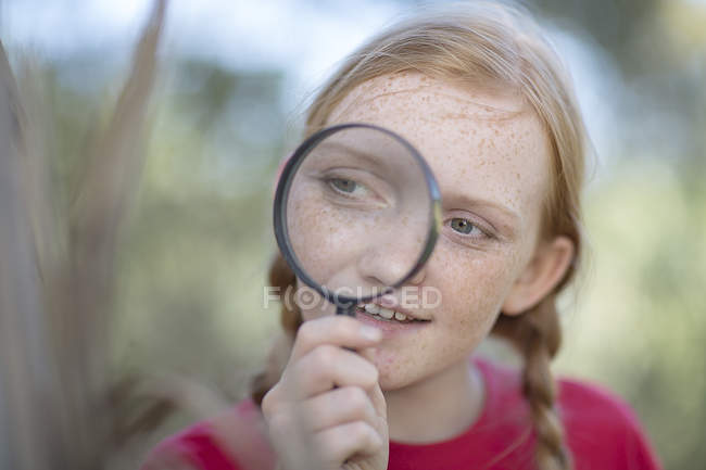 Девушка на экскурсию смотрит через увеличительное стекло — стоковое фото