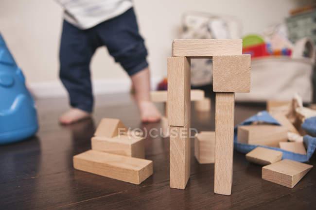 Bausteinstruktur mit Kind im Hintergrund — Stockfoto