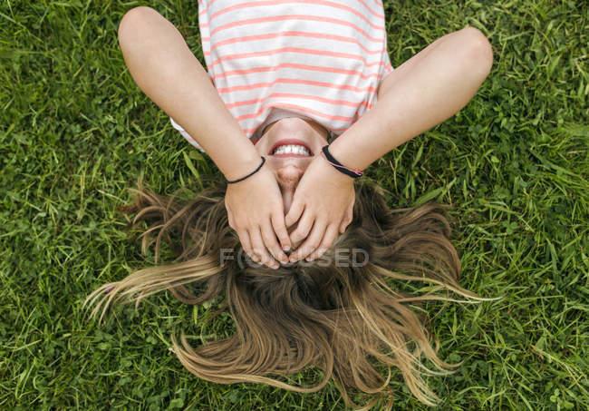 Mädchen auf der Wiese liegen und die Augen mit Händen — Stockfoto