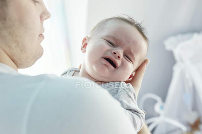 Junger Vater tröstet weinendes Baby — Stockfoto