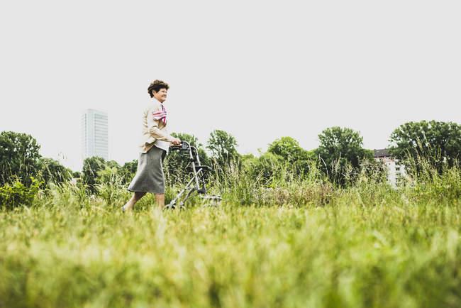 Senior woman walking with wheeled walker — Stock Photo
