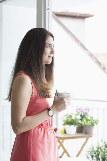 Junge Frau mit Kaffeetasse am Morgen — Stockfoto