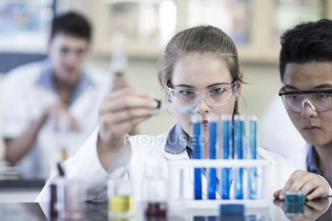 Étudiants en chimie de la classe pipetage liquide dans le tube à essai — Photo de stock