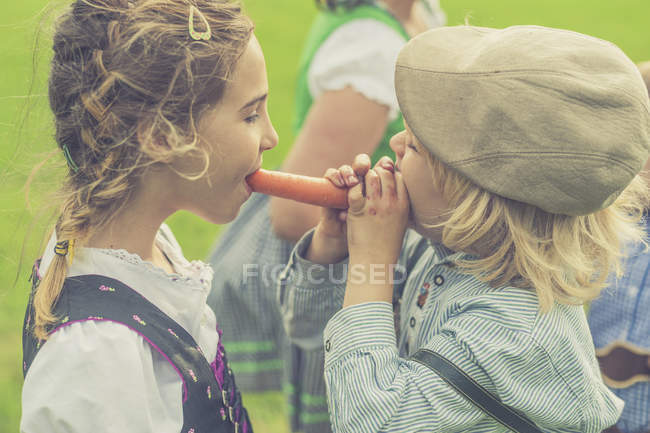 Boy and girl together biting off carrot — Stock Photo