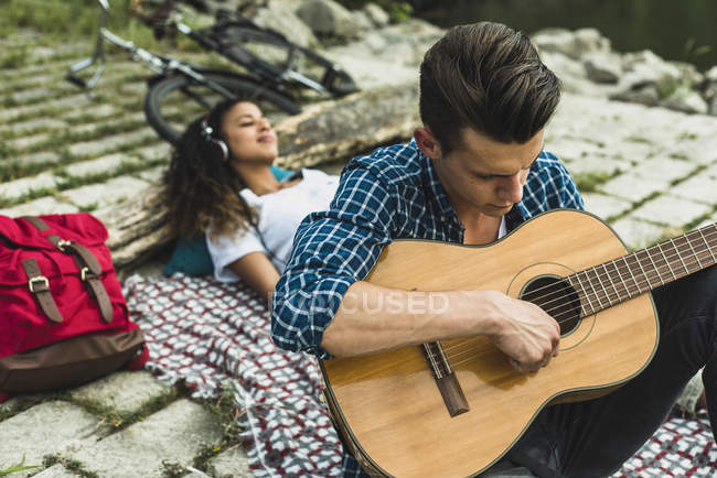 Relaxed young couple with guitar outdoors — Stock Photo