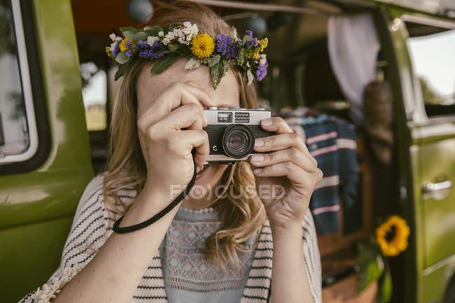 Женщина-хиппи фотографирует с аналоговой камерой перед фургоном — стоковое фото