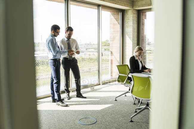 Two businessmen sharing digital tablet and businesswoman in conference room — Stock Photo