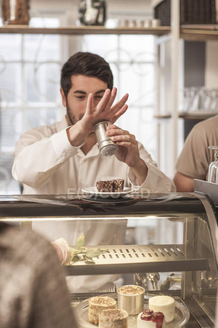 Young man at cake counter sprinkling icing sugar on cake — Stock Photo