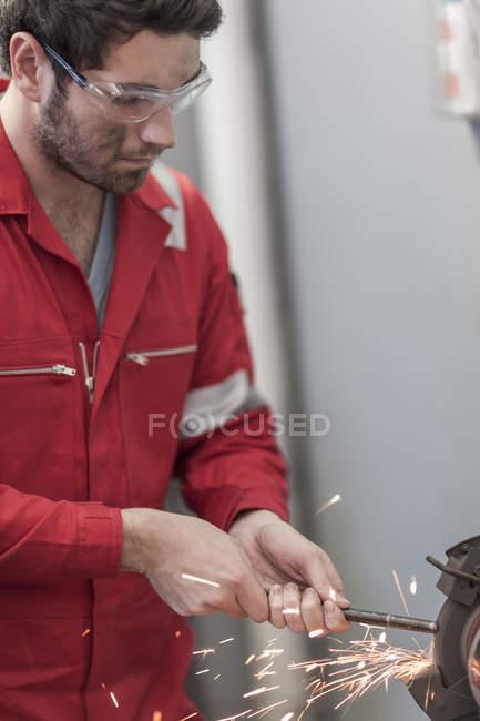 Car mechanic at work in repair garage, grinding machine — Stock Photo