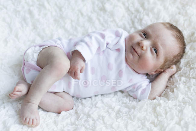 Портрет Улыбающаяся девушка новорожденного младенца, лежащего на одеяло — стоковое фото