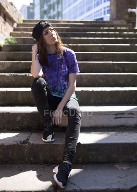 Портрет молодой женщины в бейсболке, сидящей на лестнице — стоковое фото