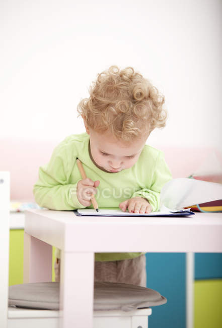 Little blond girl painting with coloured pencil — Stock Photo