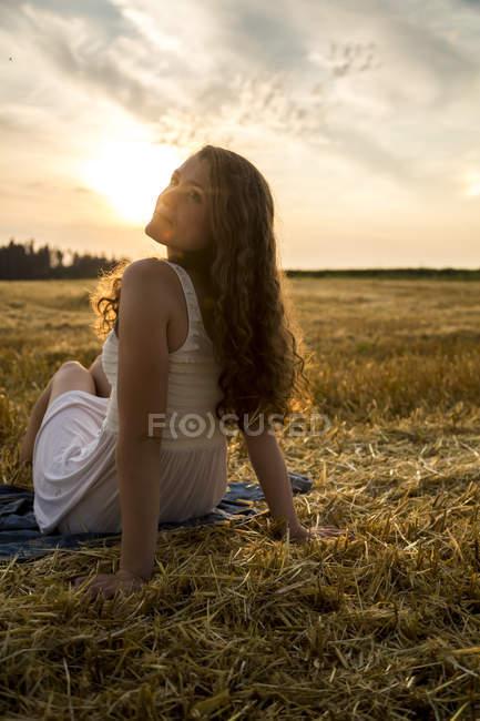 Woman sitting on stubble field — Stock Photo