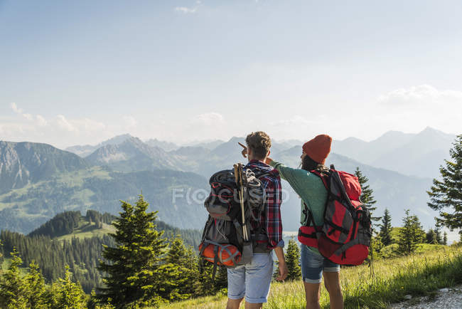 Young couple in alpine landscape looking at view — Stock Photo