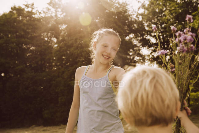 Girl and boy with bunch of thistles and meadow flowers — Stock Photo