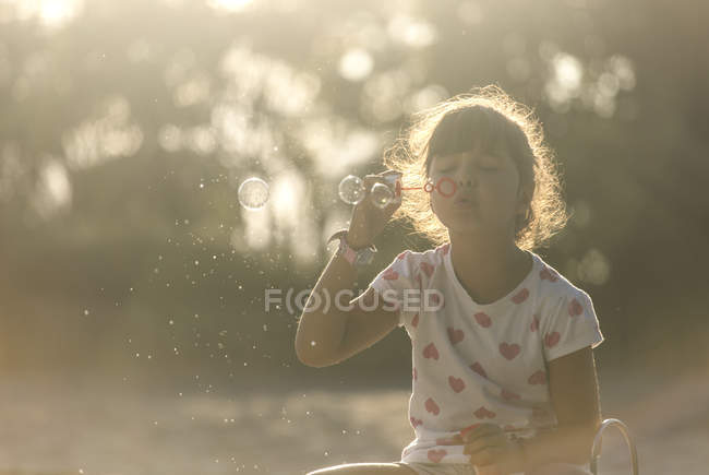 Little girl making soap bubbles in the park at twilight — Stock Photo