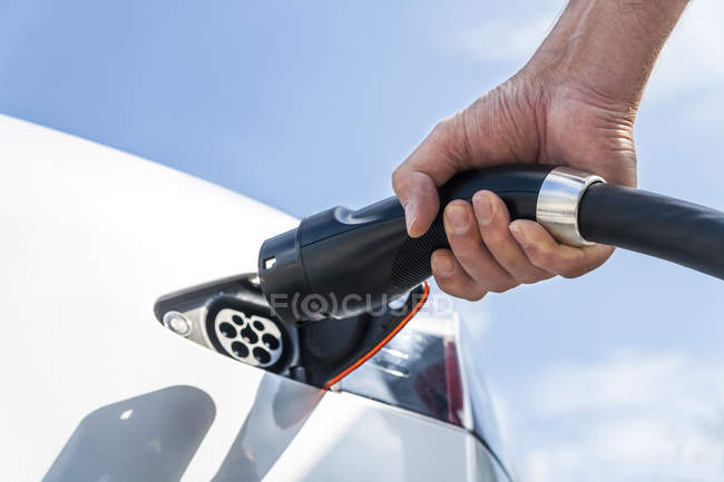 Charging of an electric car, closeup of male hand — Stock Photo