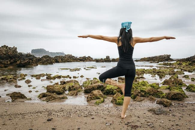 Espanha, Astúrias, Gijon, mulher fazendo ioga em uma praia rochosa — Fotografia de Stock