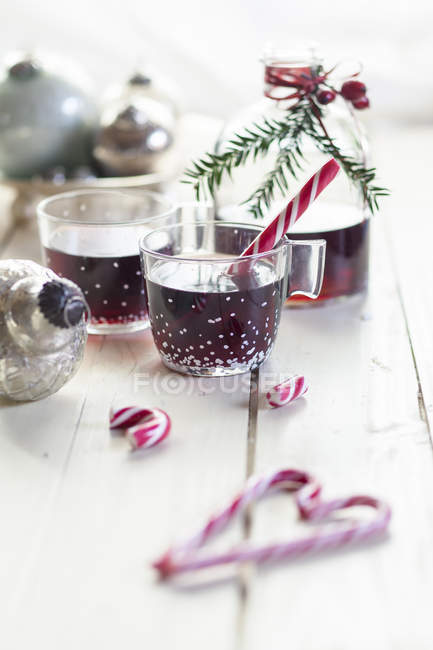 Glasses of mulled wine, candy canes and Christmas decoration — Stock Photo