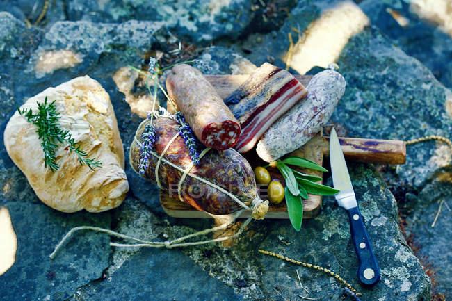 Различные колбасы, хлеба и оливки каменные поверхности — стоковое фото
