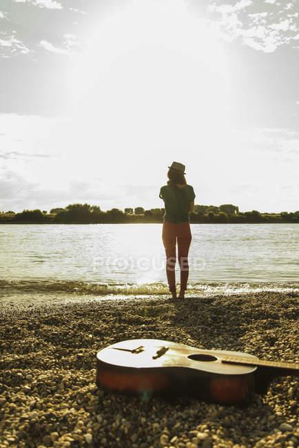 Jovem mulher em pé à beira do rio com guitarra em primeiro plano — Fotografia de Stock