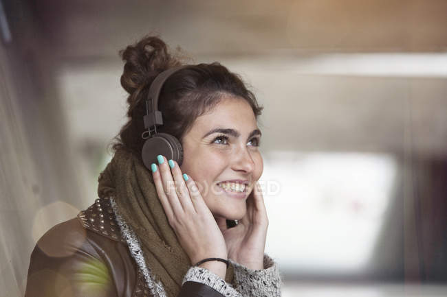 Portrait of smiling young woman hearing music with headphones — Stock Photo