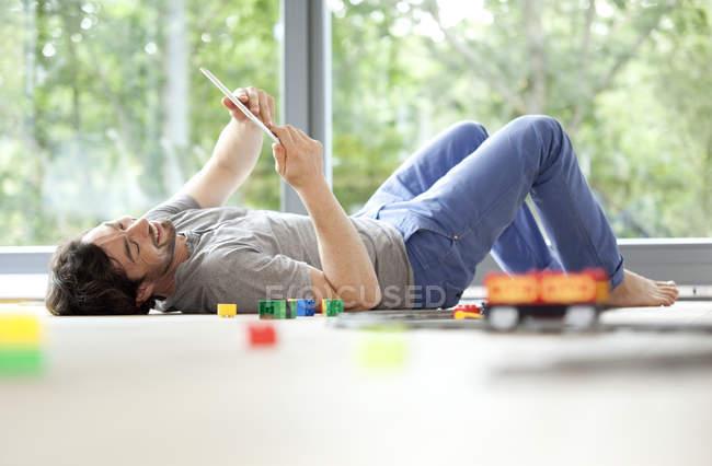 Sonriente hombre acostado en el piso con tableta digital junto a tren de juguete - foto de stock