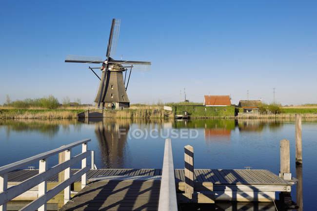Países Bajos, Kinderdijk, Kinderdijk molino contra el agua - foto de stock