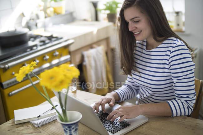 Giovane donna che utilizza il computer portatile, lavorando da casa — Foto stock