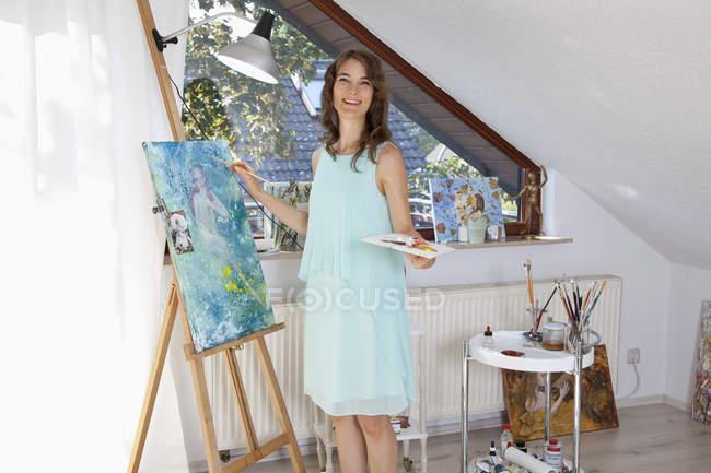 Portrait of happy painter at work in her studio — Stock Photo