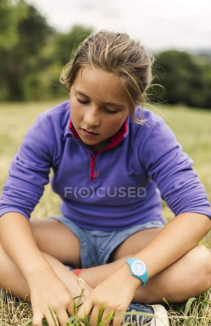 Menina sentada num prado, olhando para baixo — Fotografia de Stock