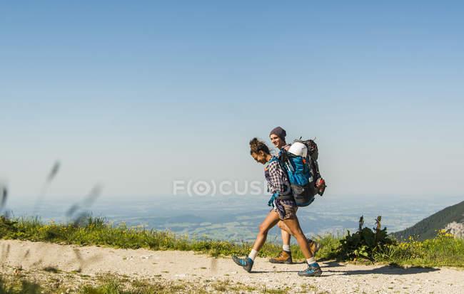 Áustria, Tirol, Tannheimer Tal, jovem casal caminhadas na trilha de montanha — Fotografia de Stock
