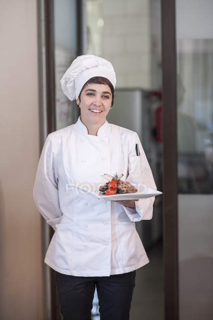 Smiling female chef serving main dish — Stock Photo
