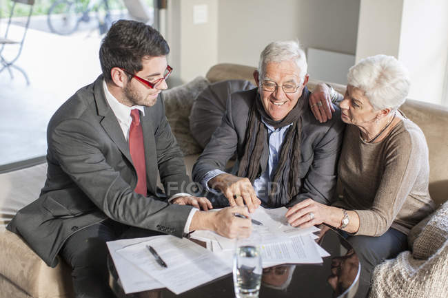 Senior couple at home having a meeting with salesman — Stock Photo