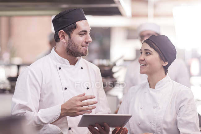 Two chefs working together in kitchen, using digital tablet — Stock Photo
