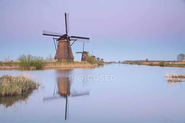 Paesi Bassi, Kinderdijk, Kinderdijk mulini a vento al crepuscolo contro l'acqua — Foto stock