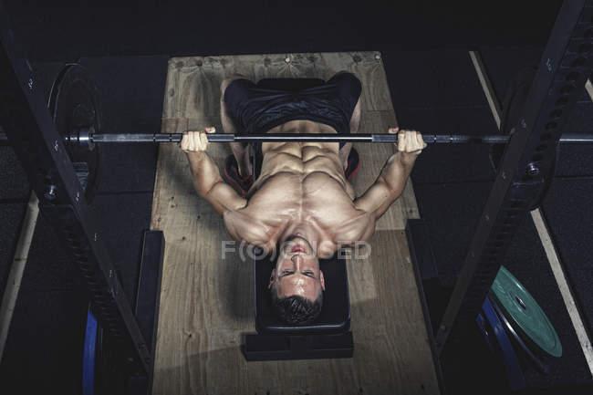 Физический спортсмен делает штанги в тренажерном зале — стоковое фото