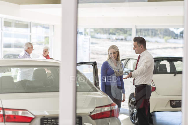 Car dealer talking to woman in showroom — Stock Photo